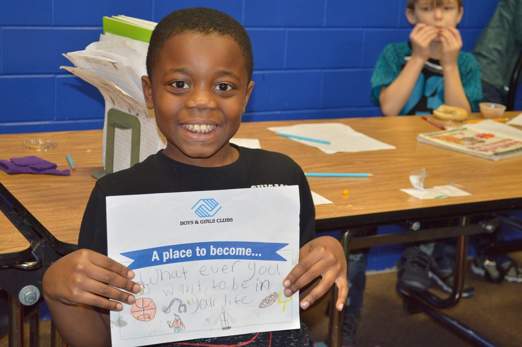 Boy holding up picture of what Boys & Girls Clubs of Muncie means to him